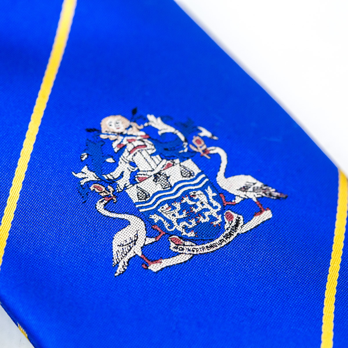Close up of blue tie with embroidered logo