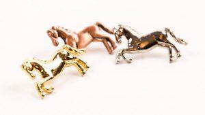 Three metal horse shaped badges