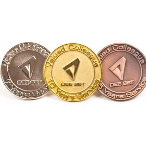 three award badges in gold, silver and nickel