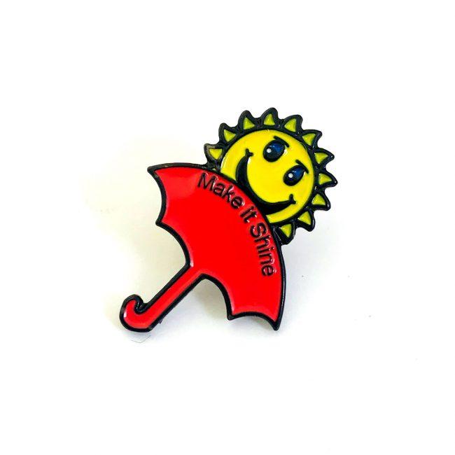 Red umbrella and yellow sun pin badge
