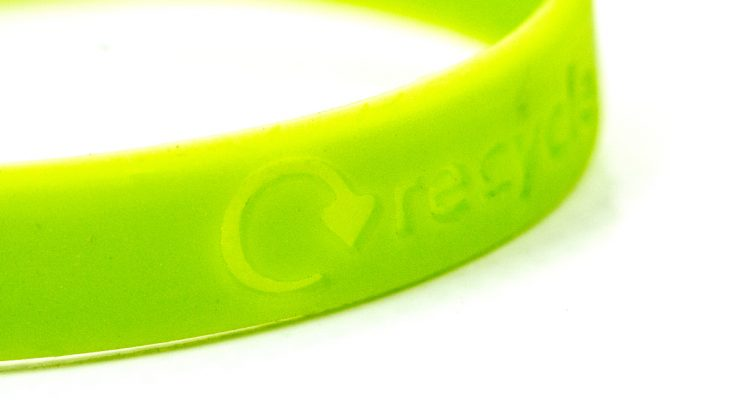 Close up of green wristband that says 'recycle'