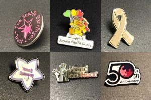 Group of metal charity badges