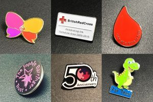 Group of six metal charity badges