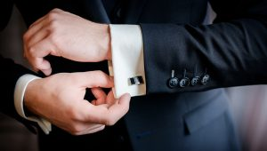Man putting on cufflinks for black tie event