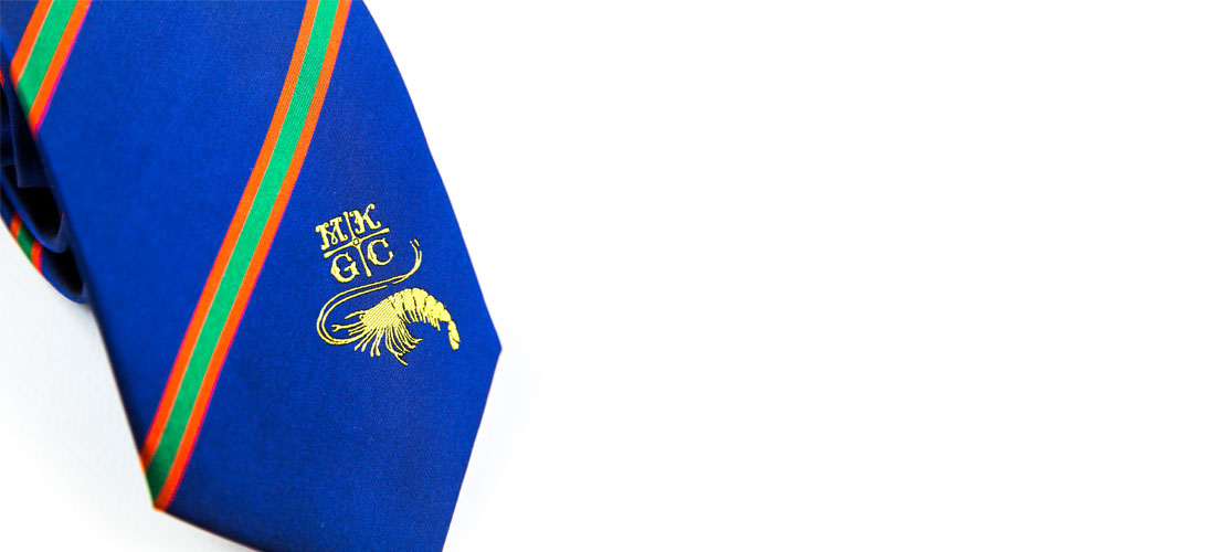 Close up of royal blue tie with green and orange stripe and gold embroidery logo