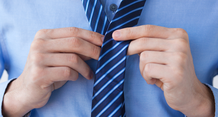 Man tying blue stripe tie