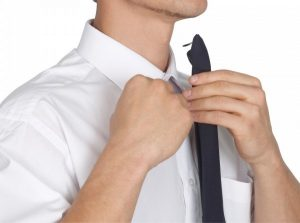 Man attaching clip on tie to his white shirt collar